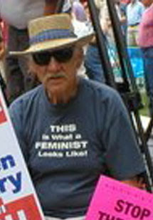 An older man with a silver moustache and a dapper hat surrounded by placards