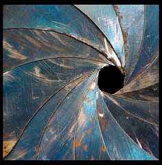 Photograph of the scarred, rusted aperture blades of an old lens