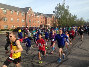 Adult and child runners take off down the Ascension Village and Blessed Trinity driveway to Puritas Avenue on a clear blue sky spring day in 2016.