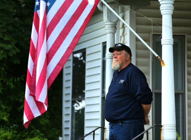 """Hudson-06/14/13-  A funeral mass was held at Saint Michael Church for former Gov. Paul Cellucci , where friends, family and politicians attended.  Resident Jim Rittenhouse watches from across the street from the church on his front steps. """"Everybody in town knew him."""" he said."""