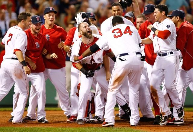Mike Napoli #12 of the Boston Red Sox is congratulated by teammates at home plate after hitting a walk-off home run in the 11th inning against the New York Yankees during the game on July 22, 2013 at Fenway Park in Boston, Massachusetts.
