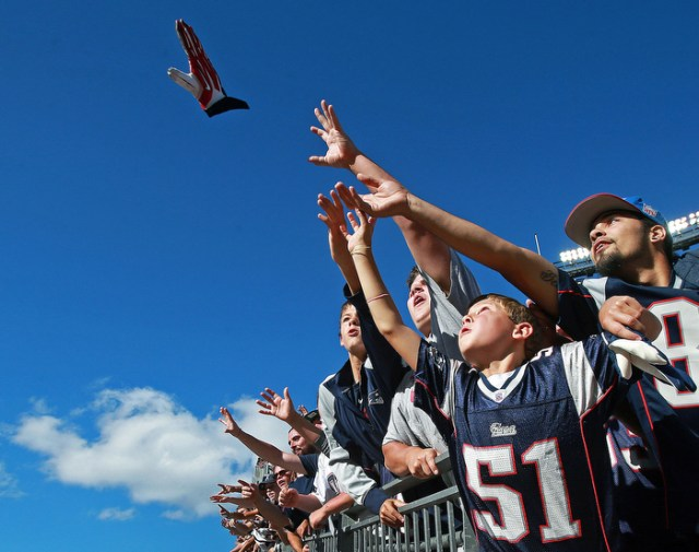 Fans vie for a glove tossed to them by a Patriots players as he leaves the field following the New England victory. The New England Patriots hosted the Tampa Bay Buccaneers in a regular season NFL game at Gillette Stadium.