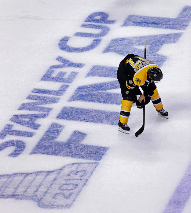 The Bruins Patrice Bergeron is bent over in despair as the Blackhawks continue to celebrate at the other end of the ice.