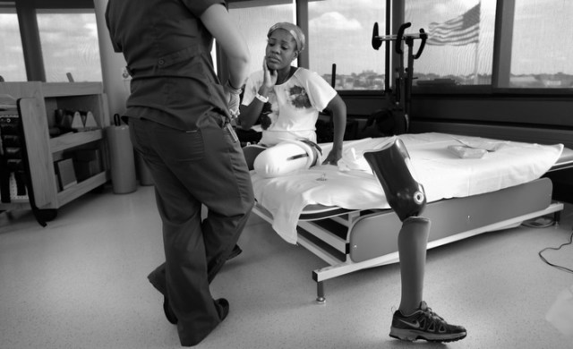 Mery Daniel, a Boston Marathon bombing survivor, pauses while she talks with her physical therapist Jessica Guilbert, as she takes a break from exercising with her new prosthetic leg, at Spaulding Rehabilitation Hospital, Wednesday, July 3, 2013, in Boston.