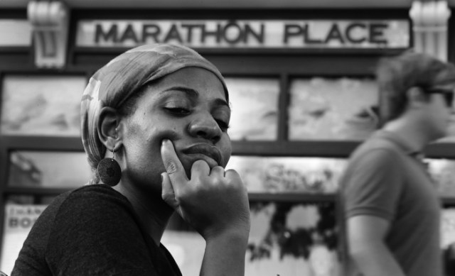 Mery Daniel, a Boston Marathon bombing survivor, pauses on Boylston Street while visiting the explosion site where she lost her left leg, Friday, May 31, 2013, in Boston.  Six weeks earlier the Haitian immigrant was standing amid a throng of spectators, watching runners complete America's most famous race, when bombs detonated, killing three and injuring more than 260 others.