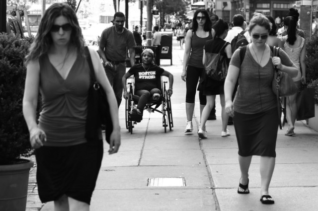 Mery Daniel, a Boston Marathon bombing survivor, heads down Boylston Street with her husband Richardson Daniel, after visiting the explosion site where she lost her left leg, Friday, May 31, 2013, in Boston.  Daniel could no longer blend easily into a crowd of women out for an afternoon walk, but hoped to regain her independence to walk again.