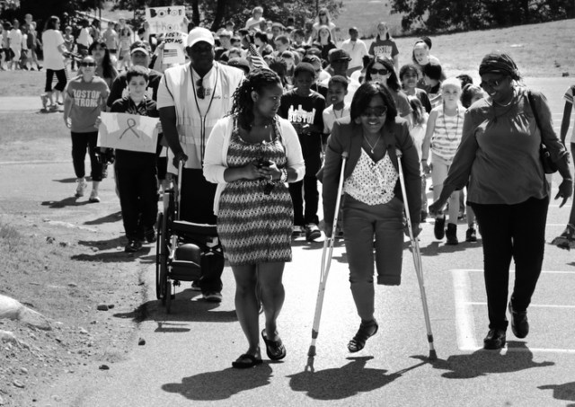 Mery Daniel, a Boston Marathon bombing survivor, uses borrowed crutches as she walks with students during a fundraising walkathon for her, at the William Seach Primary School in Weymouth, Wednesday, June 5, 2013. Students at the school raised over $8,000 for Daniel, whose father Hary Volmar, pushing wheelchair, is one of their bus drivers.  Flanking Daniel is her mother, Marie Daniel, at right, and cousin Yvrantz Celestin, at left.