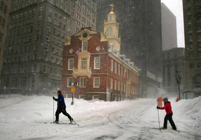 Boston-02/09/13- People began to dugout from the nearly two feet of snow from the blizzard.  Two people ski along Congress Street past the Old State House where it appeared to be a ghost town with vehicle traffic banned.