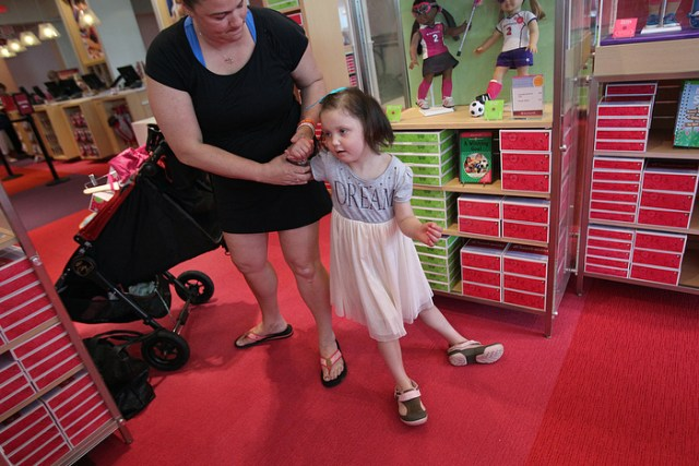 7. In June, Caroline and her mother have a shopping spree at the American Girl Doll store in Natick. Her troubling symptoms have returned--and Calle struggles for balance. The disease progressed almost daily. CarolineÕs left arm became clumsy and stopped working. Then her left leg. She started slurring her words, and facial expressions began to fade.