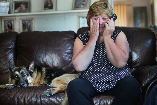 In July, Linda Pelletier is on the phone with DCF staff and has learned that her daughter Justina will not come home but will go to foster care. After the call with officials, Justina called and spoke to her tearful family. On couch is dog Roxie---who, at Justina's request, sang along with sister Julia on the piano.