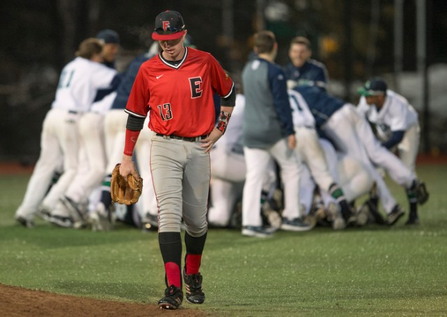 Eastern Nazarene third baseman Cameron Fiorentino walks to the dugout as Endicott players celebrate (background,) after Endicott won a dramatic victory in the bottom of the 11th inning 1-0. North Field, Beverly, MA, 03/27.