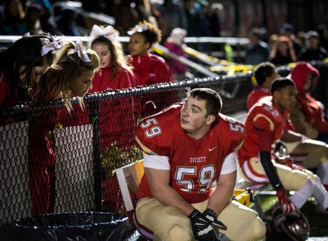 Everett high school fullback DJ MacDonald talks with school cheerleaders during the final normal season game of his high school career.