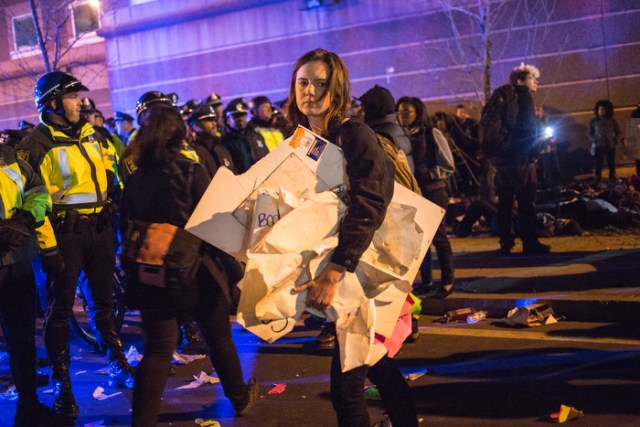November 25, 2014 – A woman collects signs from the ground as protestors retreat from the I-93 highway entrance in Boston, Mass.