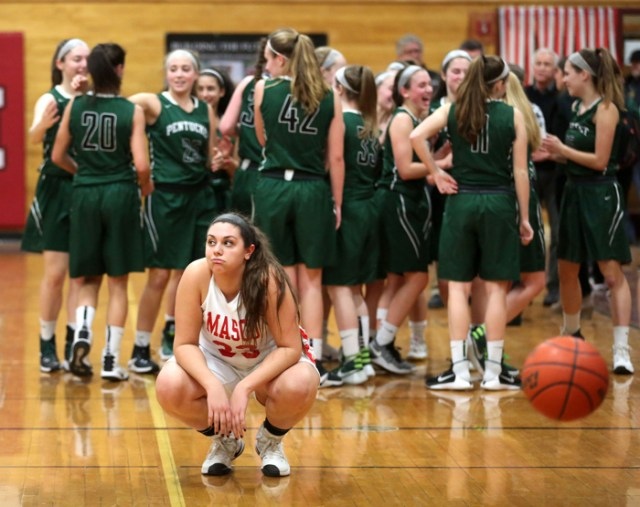 After the final buzzer rings, Masconomet senior Stephanie Mini reacts to her team's loss while Pentucket High School players celebrate behind her. Despite Masconomet's home-court advantage, Pentucket won the game 50-40.