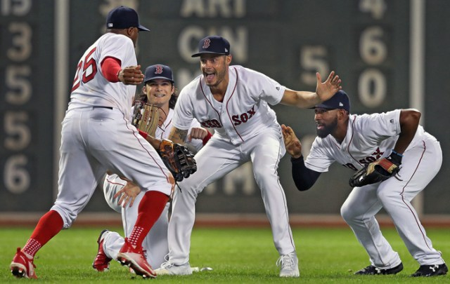 As Red Sox outfielders Rajai Davis (25,left), Andrew Benintendi, and Jackie Bradley , Jr. (right) were doing the traditional post victory fake photo shoot in centerfield, relief pitcher Joe Kelly (center) photobombed them as he ran in from the bullpen to join the party. Boston defeated Toronto 10-7.
