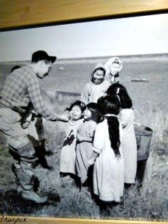 An old photo of a bush pilot visiting people in a village.
