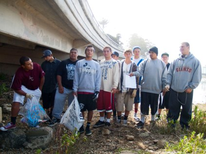 Santa Cruz High School Cardinals football players pickup trash along the San Lorenzo River below East Cliff Drive in Santa Cruz.