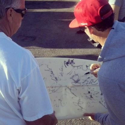 "Jason ""Ratboy"" Collins signs a surfboard"