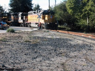 a bicyclist and a car wait as the Union Pacific blares through the Westside of Santa Cruz