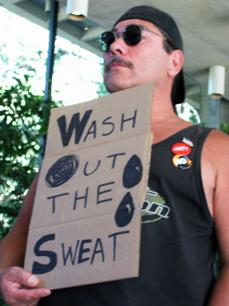 "a worker holds up a sign that reads, ""Wash Out the Sweat"""