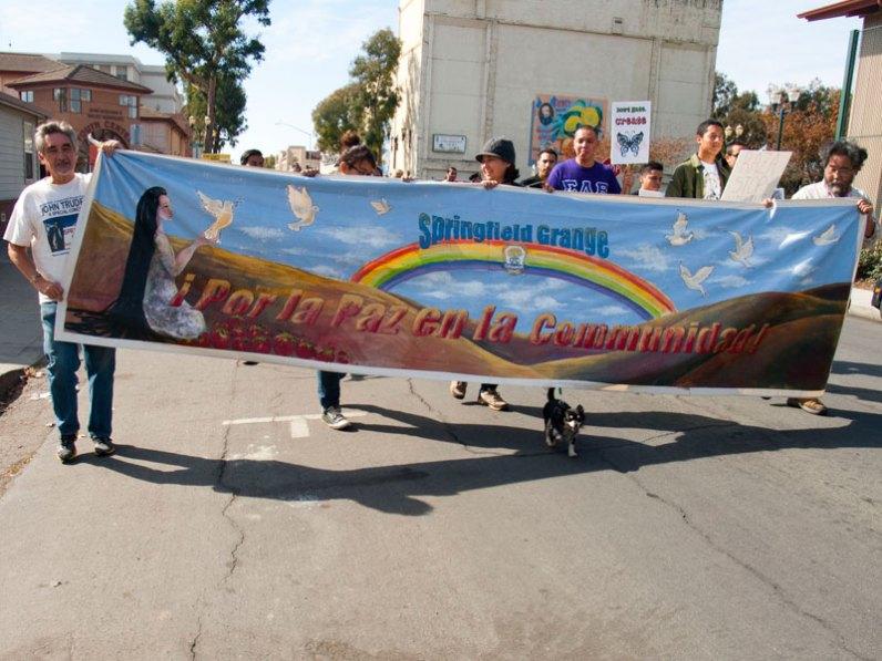 """Alan Hicks, Frances Eiliana, Aimee Mizuno, and Takeshi Mizuno hold the Springfield Community Grange banner """"Por la Paz en la Communidad!"""" painted by grange member Marlie Avant."""