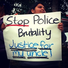 """Natalie Mendoza, Frank Alvarado's niece, held a sign reading """"Stop Police Brutality. Justice for my uncle!"""" at the July 12 rally in East Salinas."""