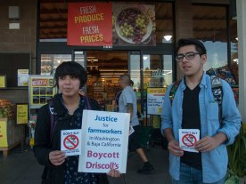 """A customer enters a Whole Foods Market in Santa Cruz holding a flyer that says, """"Don't Buy Driscoll's: Respect The Families Who Grow Your Food."""" Ruby Campos and Oscar Montiel display flyers in support the campaign."""