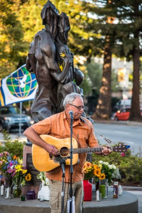 Louis LaFortune plays guitar at a peace rally on August 2, 2015 in front of the Collateral Damage statue in Santa Cruz to commemorate the 70th anniversary of the U.S. atomic bombings of Hiroshima and Nagasaki. Photo by Alex Darocy.