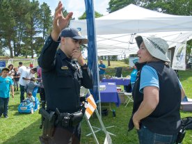 Tami Stolzenthaler, the environmental education coordinator for the city of Watsonville and main organizer of Earth Day, complains to a Watsonville Police officer that people are sharing information about the boycott of Driscoll's.