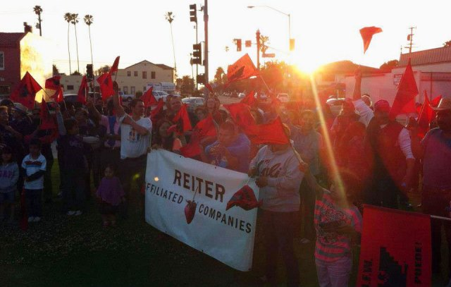 Comprehensive Immigration Reform rally in Oxnard, California on May 1, 2013, International Workers Day. Children and adults wave red and black UFW flags while holding a Reiter Affiliated Companies banner next to a company representative holding a UFW flag.