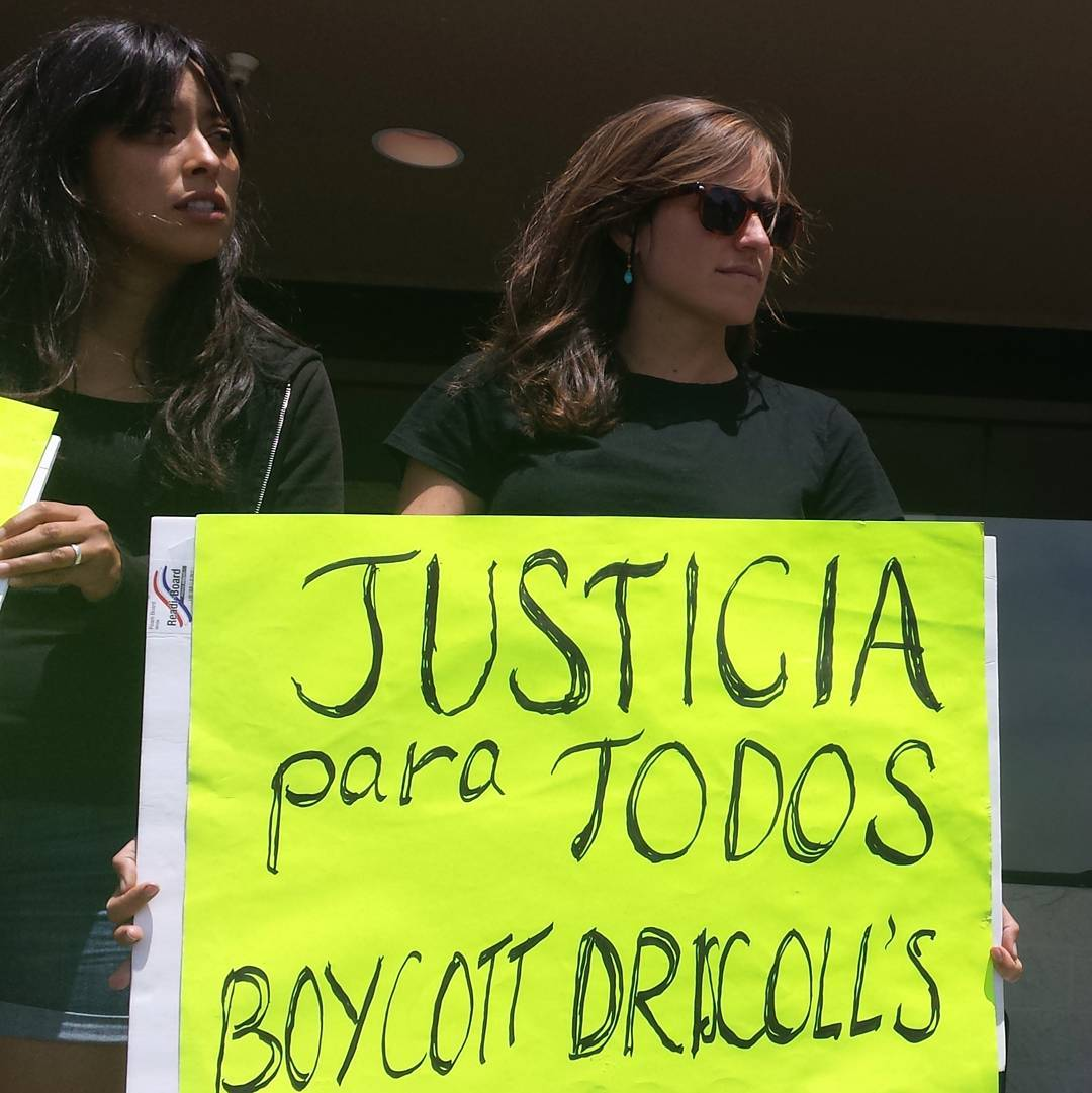 """On a busy 4th of July weekend, Vivian and Katie hold signs in front of the Safeway in Watsonville, California advocating """"Justice for All"""" and to """"Boycott Driscoll's."""" July 2, 2016."""