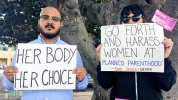 """Counter-protestors on Cedar Street hold signs stating """"Her Body, Her Choice"""" and """"'Go Forth And Harass Women At Planned Parenthood' -Said Jesus - Never"""""""