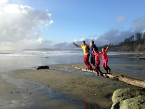A photo of Bree and Brad with their girls jumping off a log.