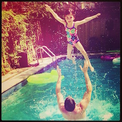 An image of Brad throwing his youngest daughter into the air in the swimming pool