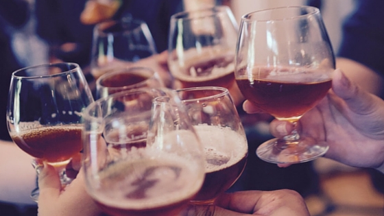 Is alcohol healthy? Photo of people toasting with a glass of beer