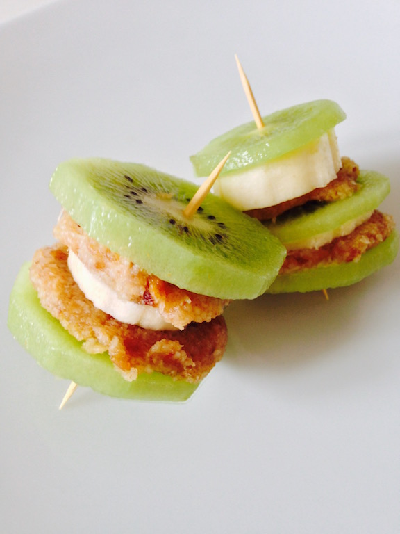 "Very easy and cute, these Kiwi Banana Stacks are made a coconut ""icing"" and sliced banana sandwiched between two slices of fresh kiwi, as shown in this photograph."