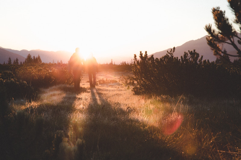 A photo of two people walking in the morning light.