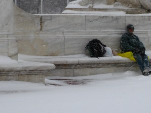 An addressless man sitting on a yellow plastic bag in the snow.