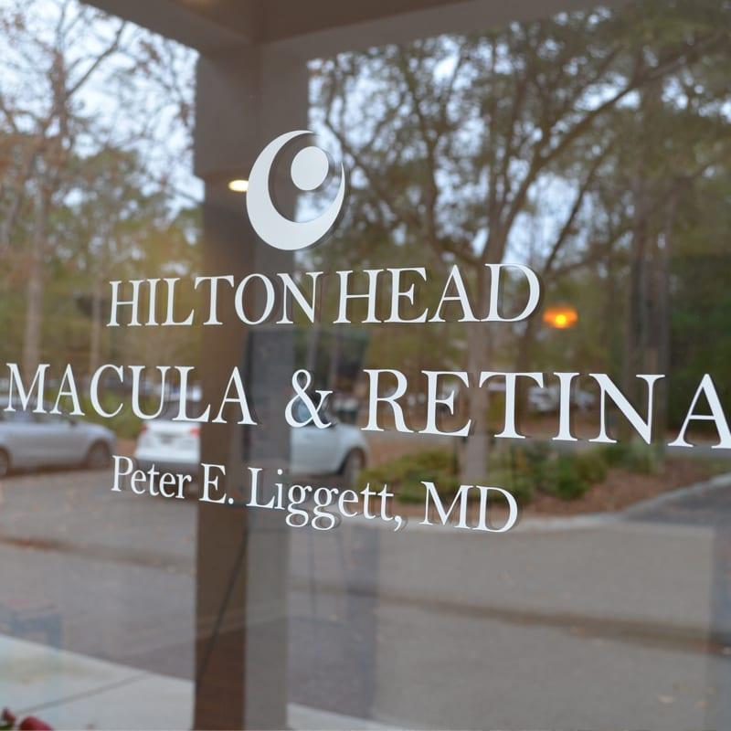 Vinyl logo of Hilton Head Macula & Retina Peter E. Liggett, M.D. on a glass door with a reflection of a parking lot