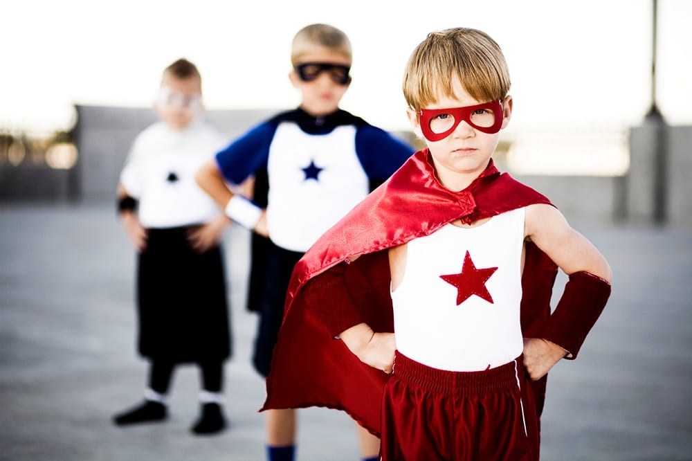 A little boy with a red cape and mask stands in the forefront of two other little boys dressed as super heroes