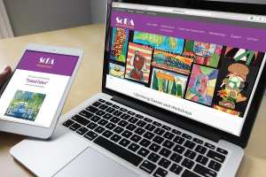An open laptop displays a colorful website for a non-profit art association and a tablet held by a hand shows an blast