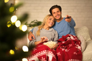 Young couple sitting under a blanket together watching TV