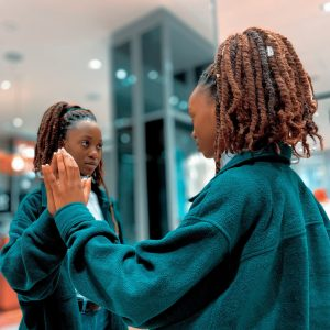 African Canadian woman looking into the mirror her hand is extended to the mirror as though she is touching her hand to another