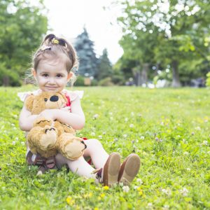 pretty-girl-sitting-green-grass-cuddling-her-teddy-bear_23-2147893054