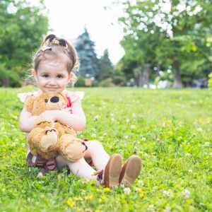 pretty-girl-sitting-green-grass-cuddling-her-teddy-bear_23-2147893054