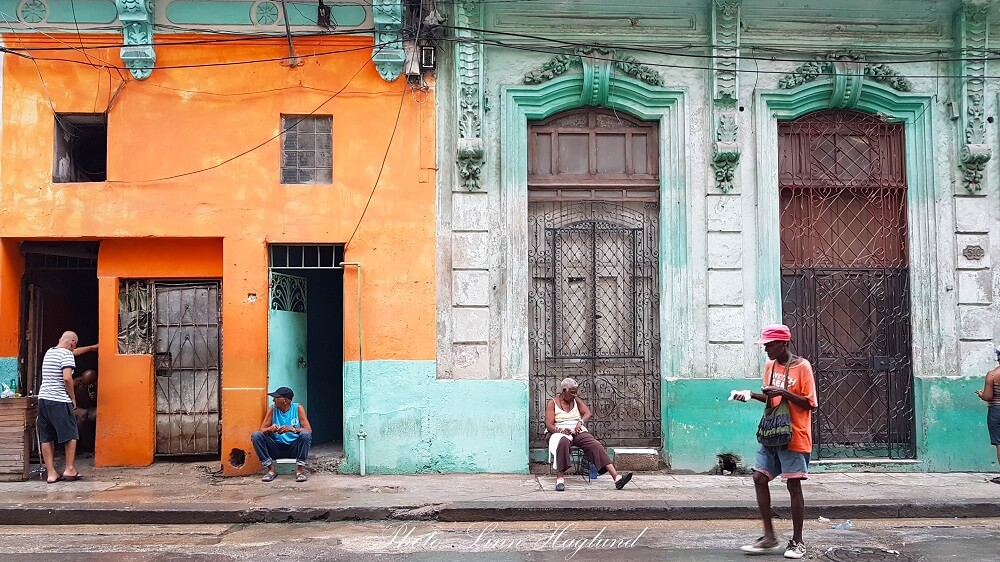 Daily life in Havana - people haning out in front of colorful houses. This is the real Cuba