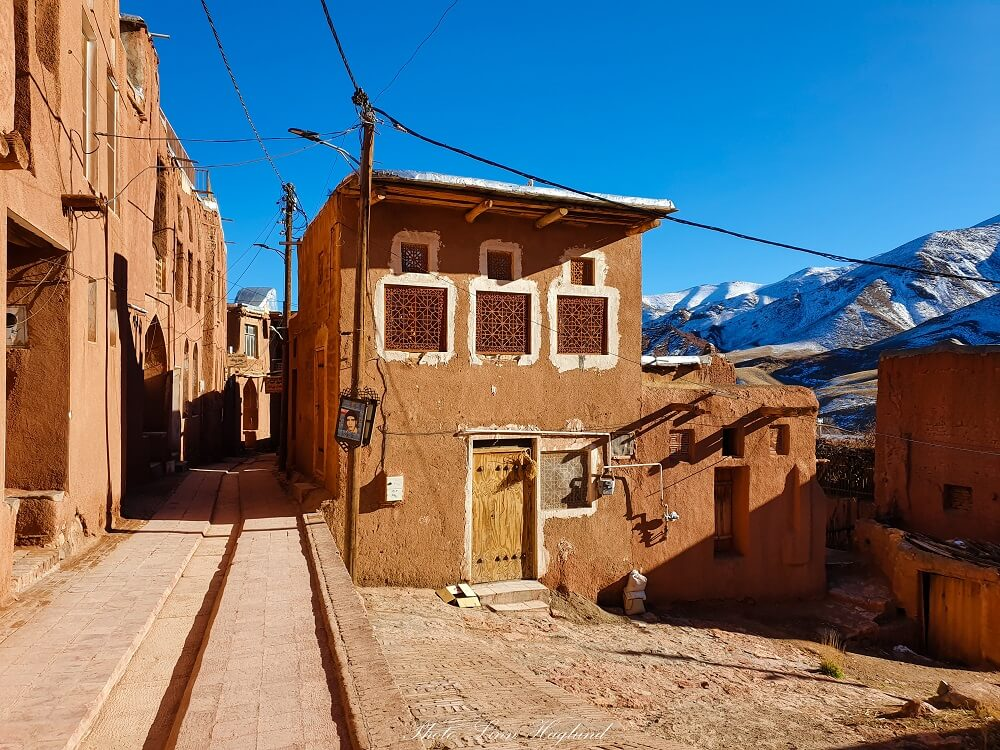 The red village of Abyaneh Iran with white-capped mountains behind