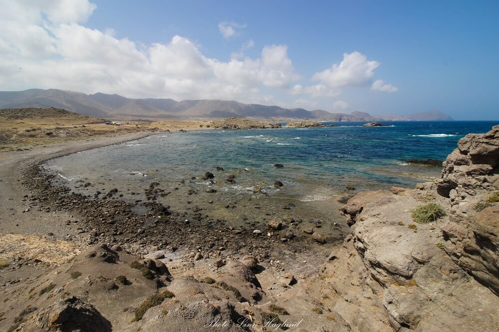 A virgin beach surrounded by rocky ground and mountains in the far back