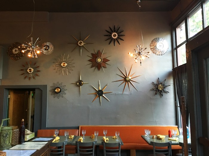 Clocks shaped like stars on the wall and dining table set at The Slide Inn