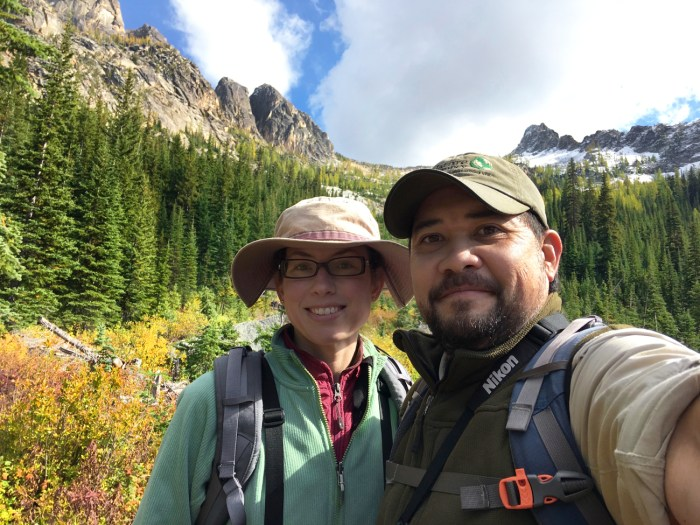 Michael and Christina halfway along the Blue Lake Trail where it opens into a meadow with mountain peaks in the background